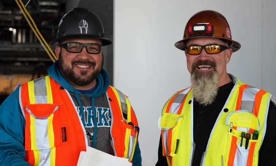 Two men with beards wearing construction hats and vests, one holding papers, smiling to the camera.
