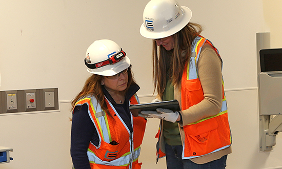 Two women in construction protective gear, one holding an iPad and both looking at it in discussion.