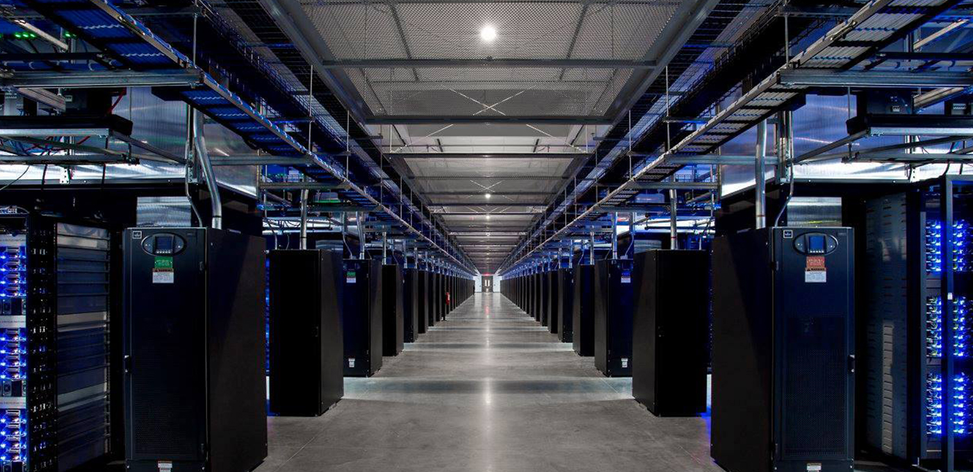 Perspective view looking between two rows of data center racks with blue lights flashing throughout.